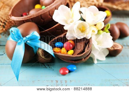 Chocolate Easter eggs with flowers on wooden table, closeup