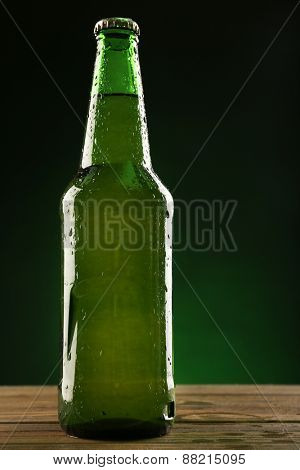 Glass bottle of beer on dark green background