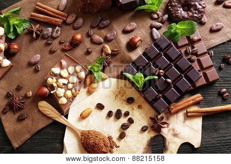 Chocolate with mint, spices and coffee beans on table, closeup