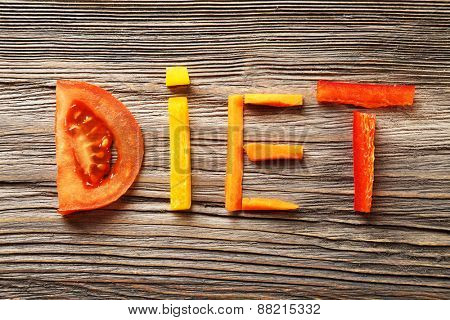 Word DIET made of sliced vegetables on wooden background