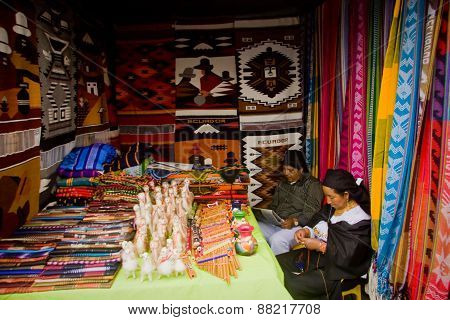 Unidentified indigenous couple in a colorful textile stall in the popular Otavalo market, Ecuador