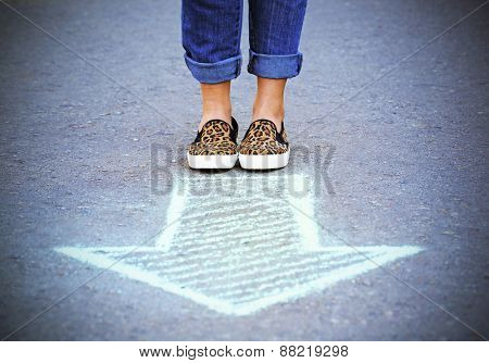 Female feet and drawing arrow on pavement background