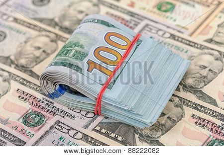 Folded Dollar Bills Wrapped By Rubber Lying Over  Banknotes