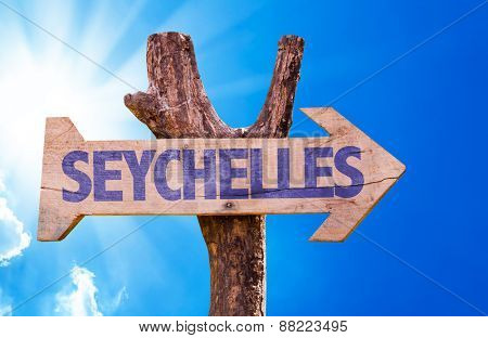 Seychelles wooden sign with sky background