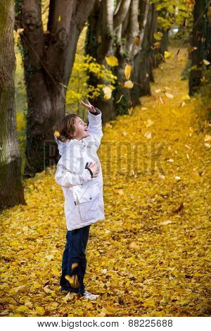 Boy Playing With Yellow Autumn Leaves In A Park
