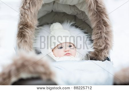 Sweet Little Baby Sitting In A Winter Fur Stroller On A Snowy Day