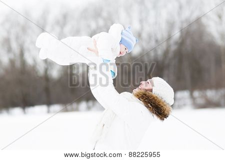Young Mother And Her Baby Playing In The Snow