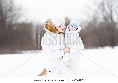 Young Attractive Woman Playing With Her Baby In A Snowy Park