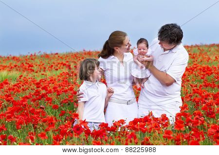Beautiful Young Family With A Son And Newborn Daughter In A Red Flower Field