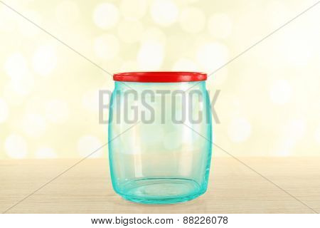 Empty glass bottle on table on bright background