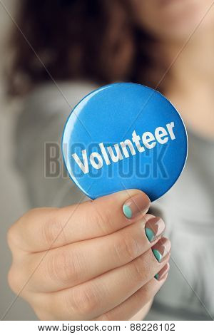 Round volunteer button in hand close-up
