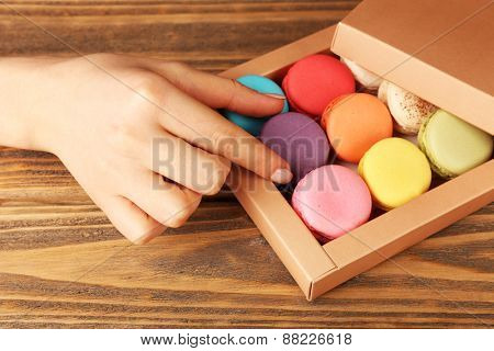 Female hand taking tasty colorful macaroons from present box on rustic wooden planks background