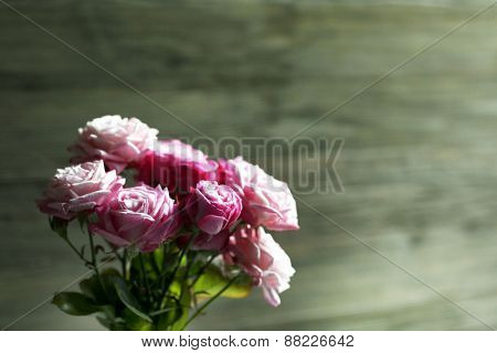 Bouquet of beautiful fresh roses on wooden background