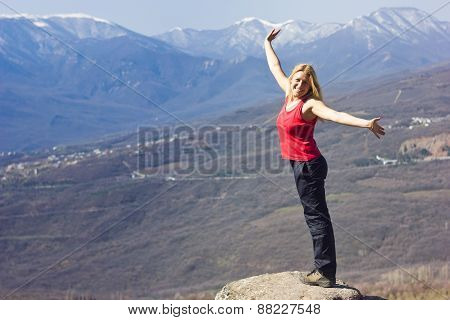 girl standing with hands-up on a cliff in the mountains  and smiling