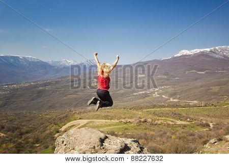 girl jumping with hands up in the mountains against sun