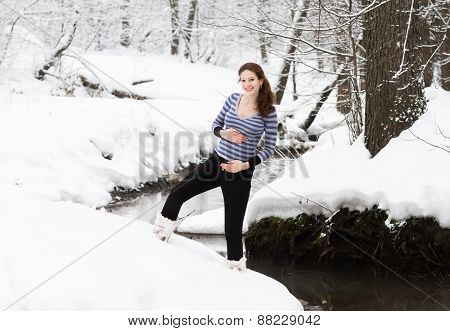 Active Pregnant Woman Walking Along A River On A Snowy Winter Day