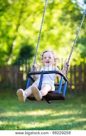 Adorable Baby Girl With Big Beautiful Eyes And Curly Hair Having Fun At A Swing On A Playground
