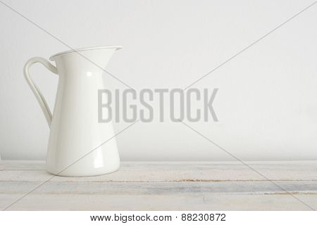 Old white vase on the white wooden shelf. White background.