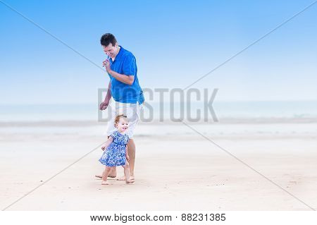 Young Father Playing With His Cute Toddler Daughter Running On A Beach