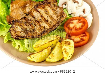 Grilled meat dish with tomato potatoes and mushrooms isolated on white