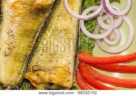 Baked shad with vegatables at dish close up