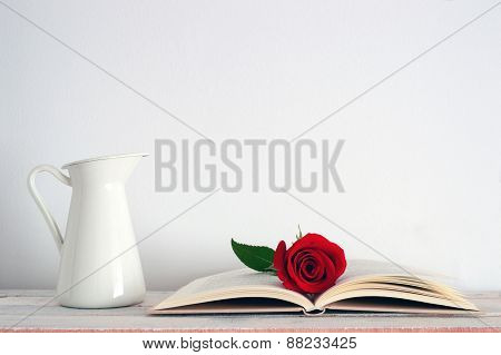 A vase and a red rose flower on an open book.