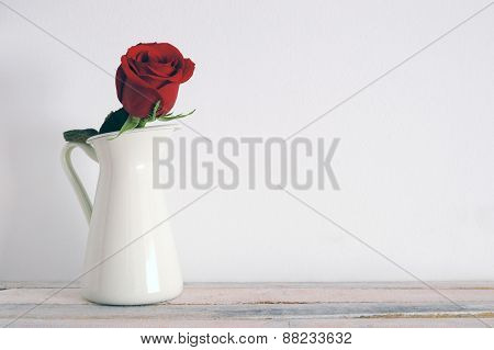 A red rose on a white vase