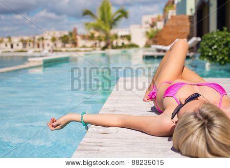 Woman in pink bikini relaxing by the pool