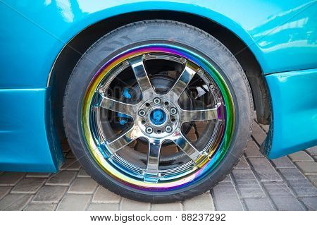 Car Wheel On Colorful Metallic Disc, Close Up Photo