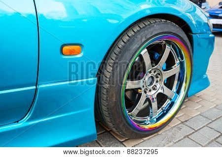 Car Wheel On Colorful Metallic Disc, Closeup Photo
