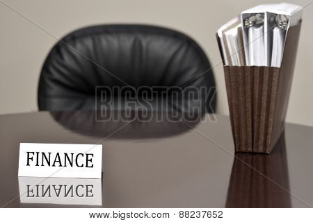 Business card for finance loans lending on desk with files and chair