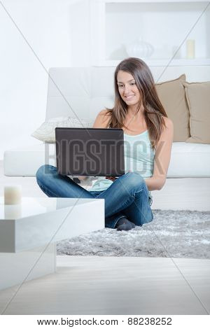 Woman sat on the floor with laptop