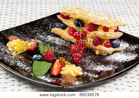millefeuille with berries on a dark caramel plate