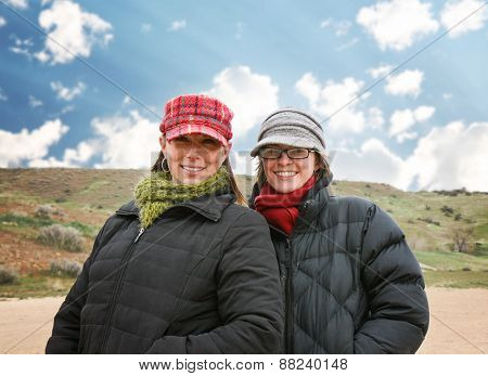 two women enjoying the outdoors on a brisk winter day at a local dog park