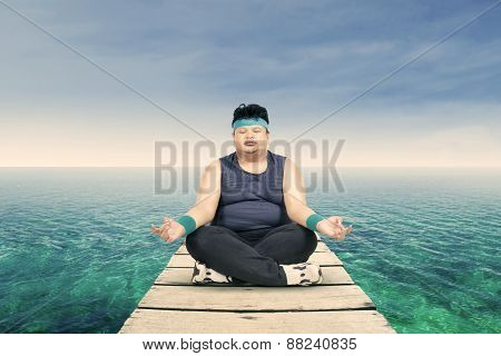 Overweight Man Meditating On The Jetty