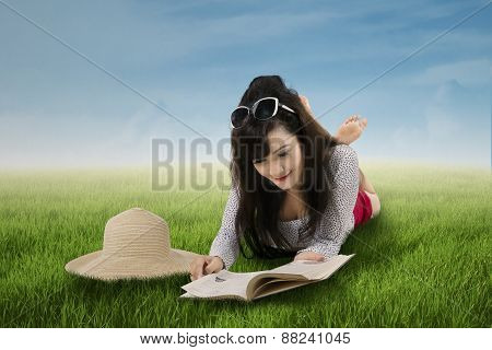 Pretty Woman Reading Book On The Park