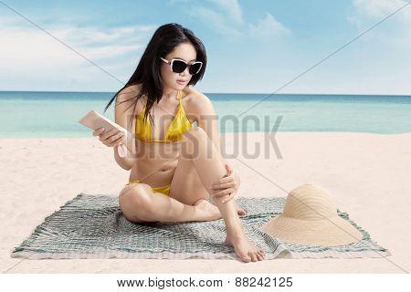 Sexy Girl Using Sunscreen At Seashore