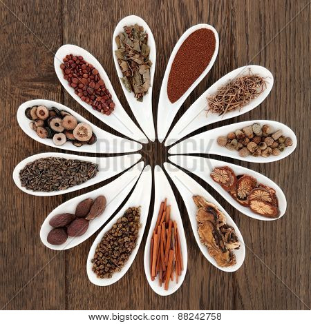 Chinese herbal medicine selection in porcelain dishes over oak background.