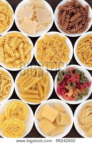 Italian pasta  shapes in white porcelain bowls.