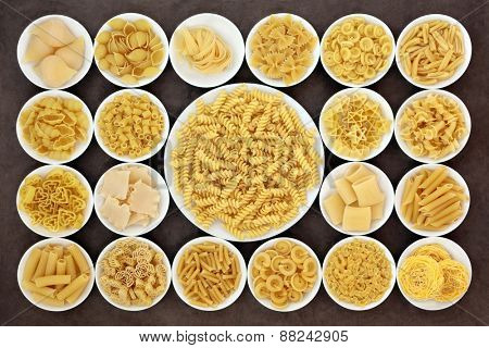 Large pasta dried food selection in round bowls over brown background.