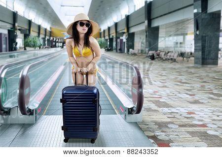 Woman With Bikini In Airport Corridor