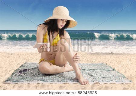 Woman Using Sunscreen On Leg Skin