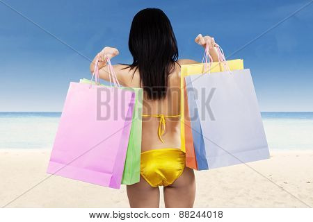 Woman with shopping bags on beach