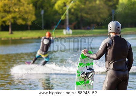 Male wakeboarder waches the performance of another athlete