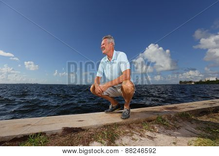 Senior man squatting by the seawall
