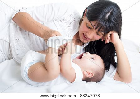 beautiful young mom staring at her small cute baby
