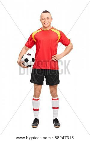 Full length portrait of a young soccer player holding a ball, smiling and posing isolated on white background