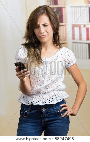 young beautiful hispanic woman using her cell phone texting