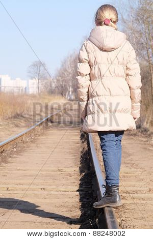 Teenage girl walking on the railway tracks