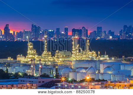 Oil refinery at twilight with city background